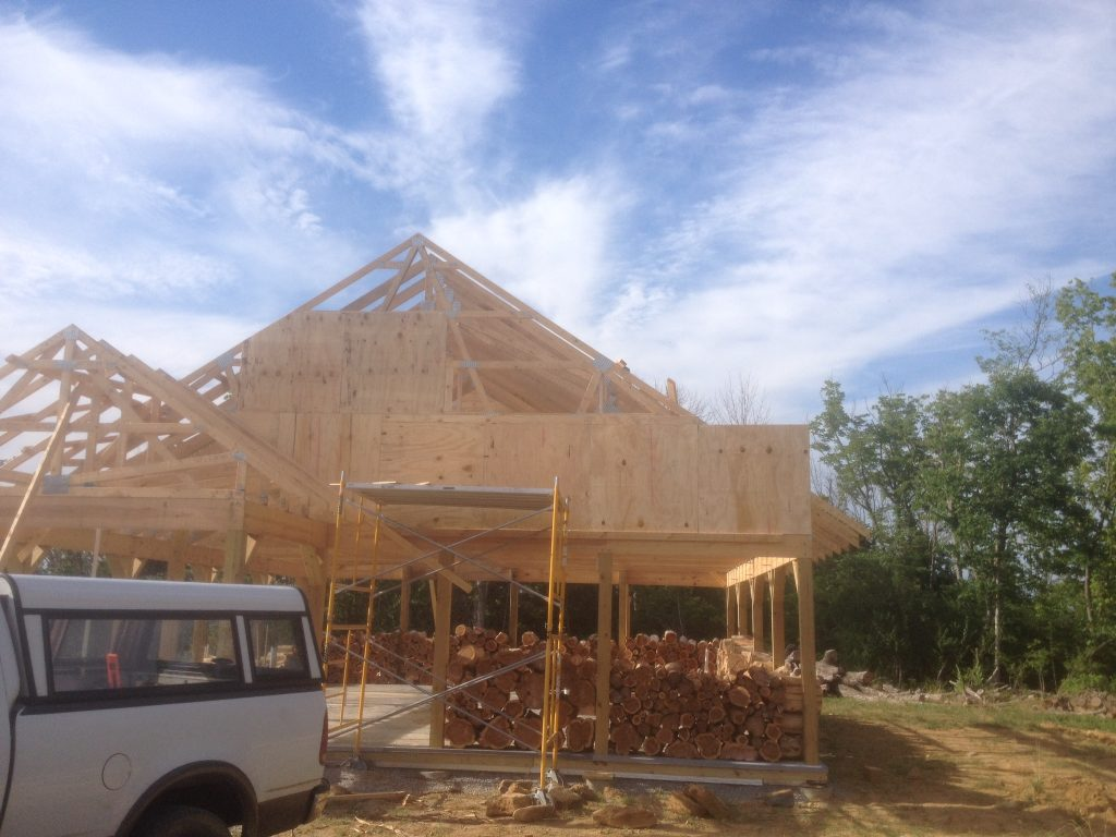 Putting up the sheathing on the front of our cordwood house (yes, we know that one corner is a little wonky...check out the progress here!)