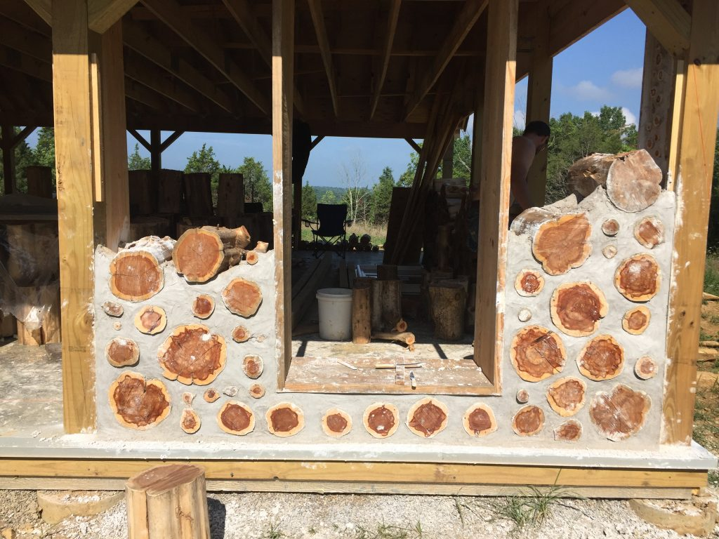 A cordwood wall in progress on a house