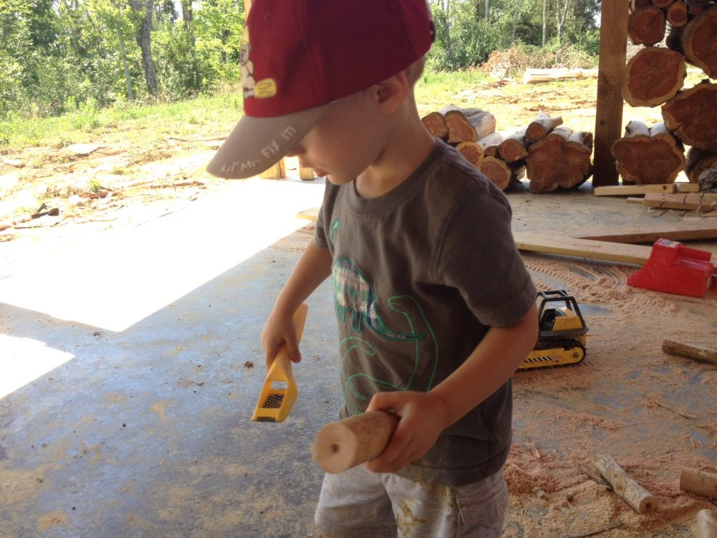 Even a three year old can help with cordwood building! Here is our son scraping the edges of a log.