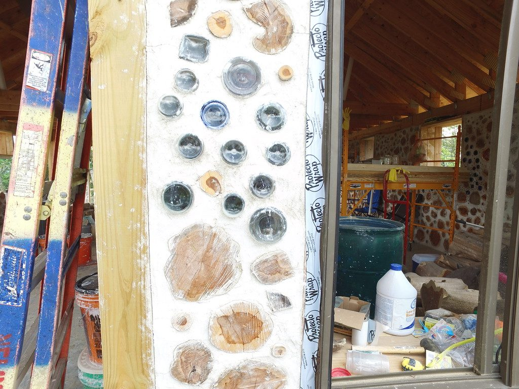 What bottle ends look like from the outside of a cordwood wall - Looking from our hill at Big Muddy Rock - accidentalhippies.com