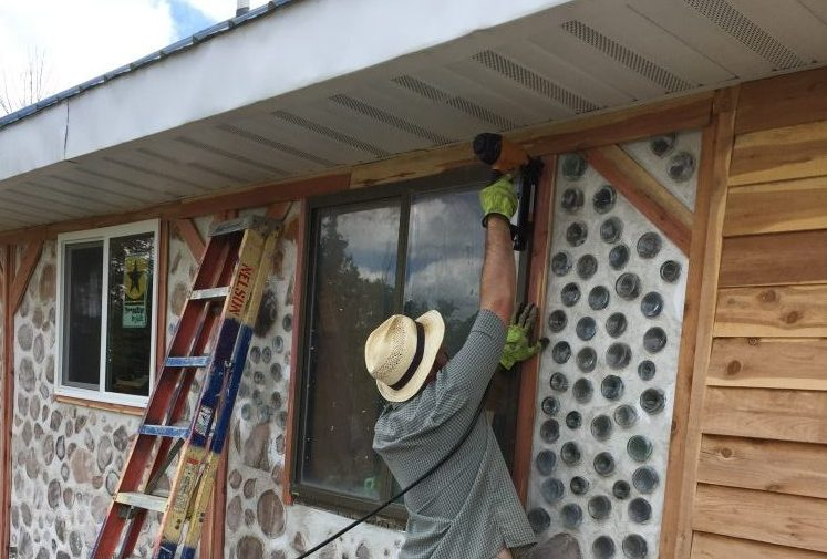 Putting up rough cedar to trim the windows on a cordwood house
