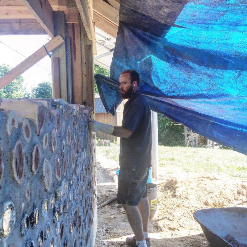 Man laying a cordwood masonry wall under a blue tarp