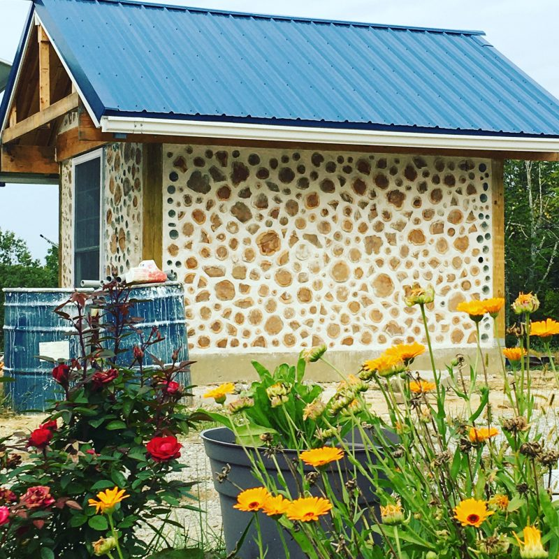 Cordwood shed with blue roof and flowers in foreground