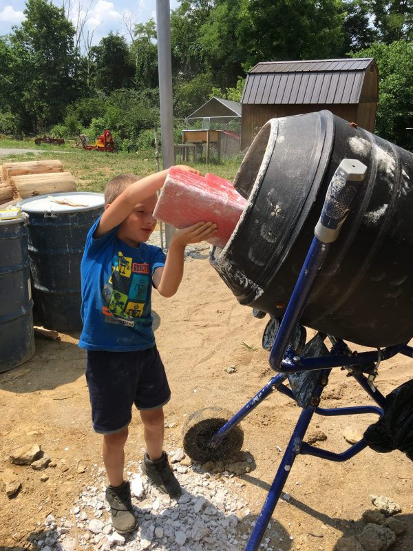Child pouring sand into mortar mixer